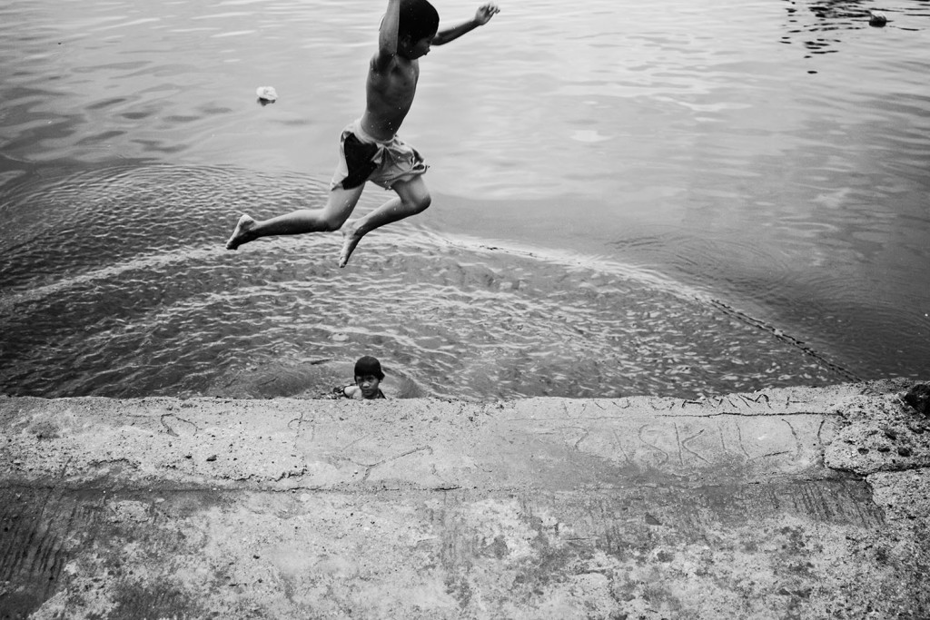 Two children are swimming in the polluted Pasig river in the Baseco slum area in Manila, Philippines, November 2013.