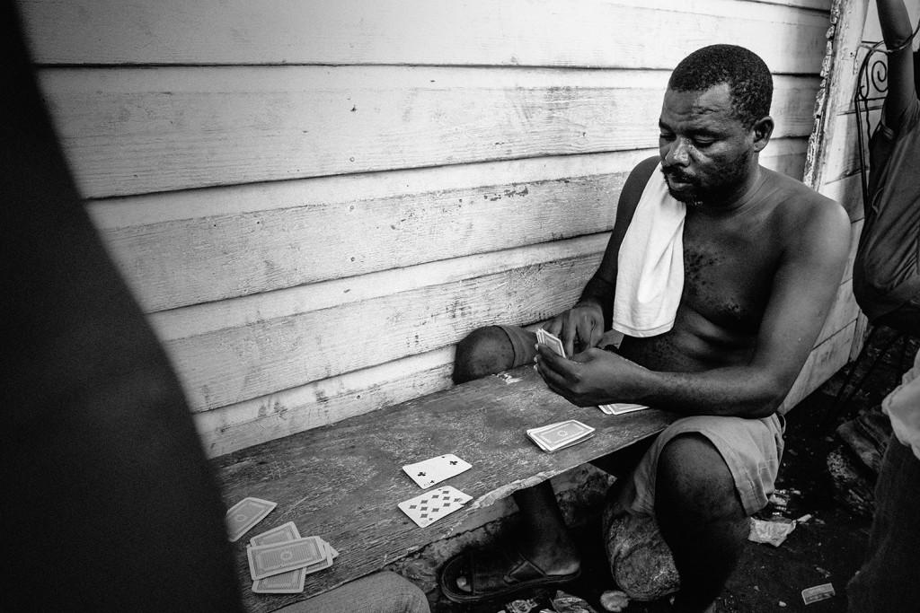 Men playing cards in a narrow side street in Cité Soleil
