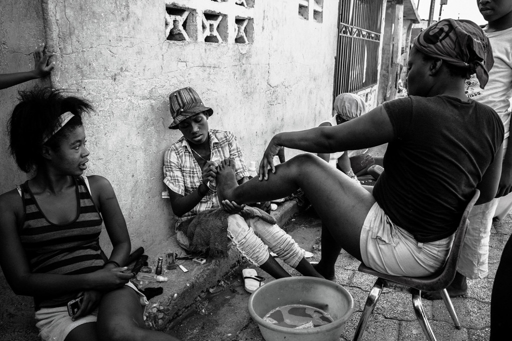Women pedicure their feet on one of the main roads of their quarter inside Cité Soleil