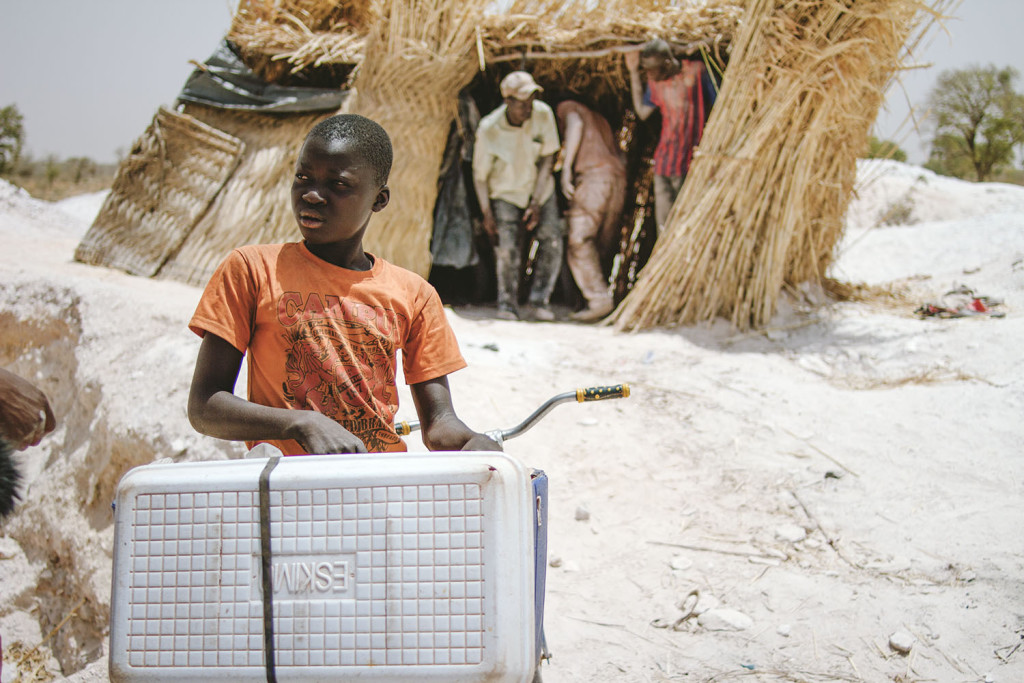 A boy sells water in a gold mine near Bouda in Burkina Faso, March 2014