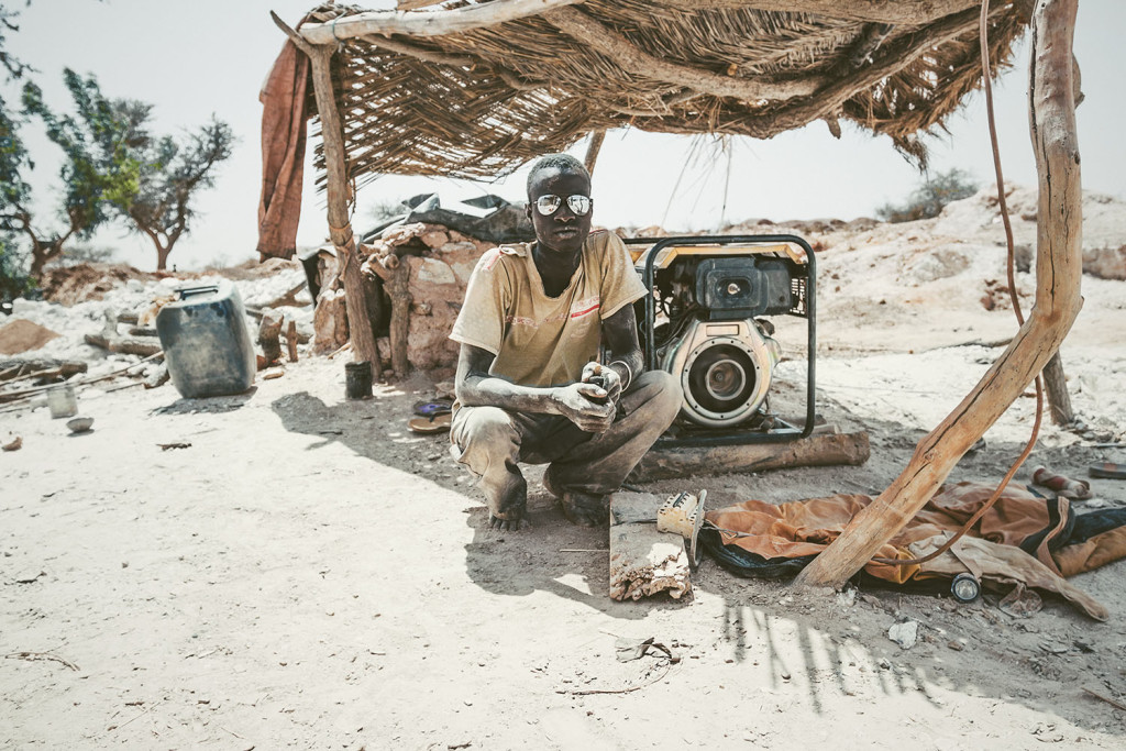 A miner squats in front of a generator used to pump water out of the mine shafts of an artisanal gold mine at Bouda in Burkina Faso, March 2014