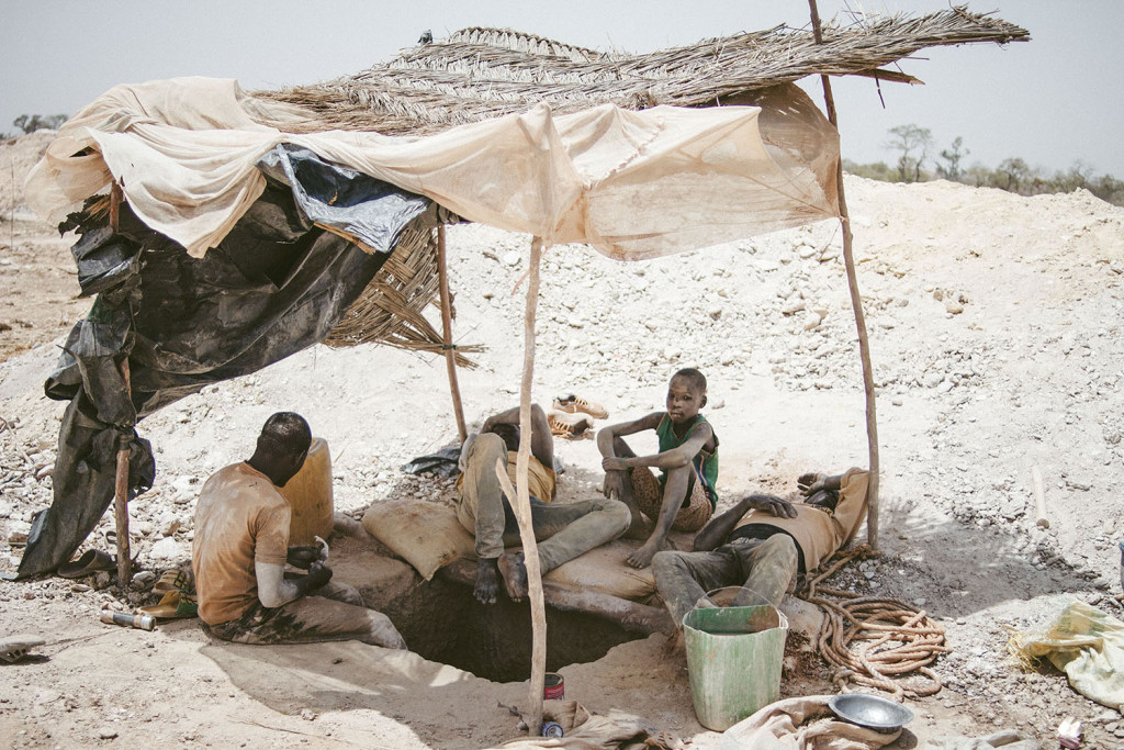Miners rest in the shadow in a gold mine near Bouda in Burkina Faso, March 2014