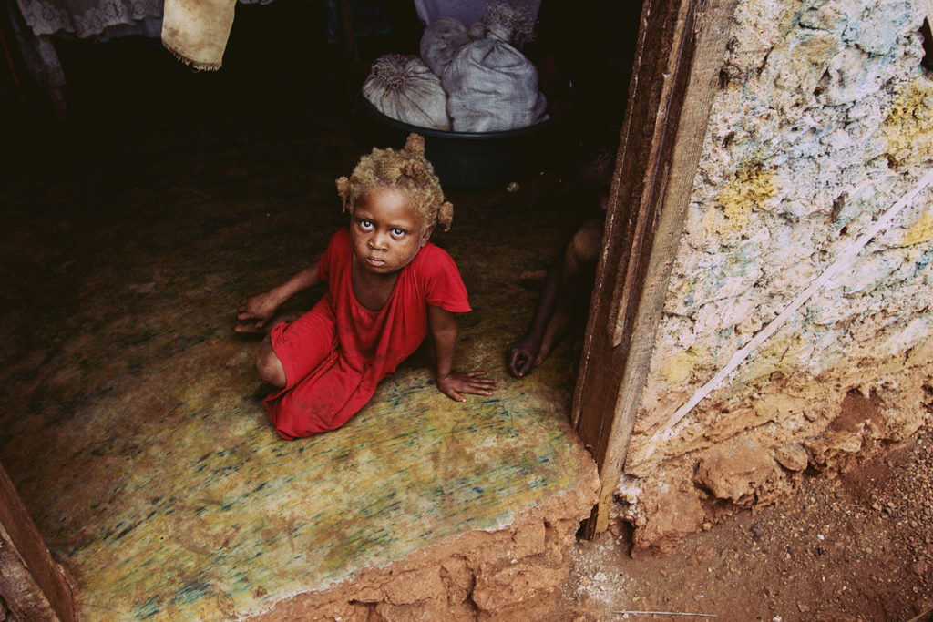 A girl sits on the floor of her family's house in a village near Jacmel, Haiti, 2014