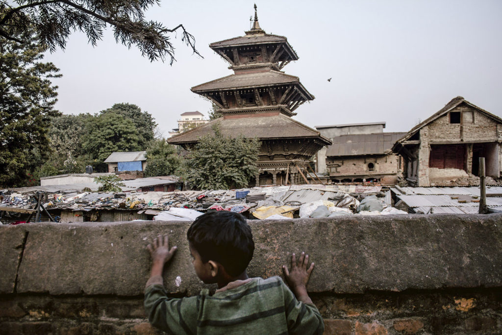 A boy plays in front of a temple somewhere in Kathmandu, 2015