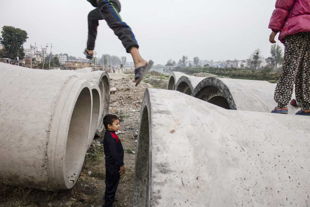 A group of children plays on some building material in Kathmandu, Nepal, 2015