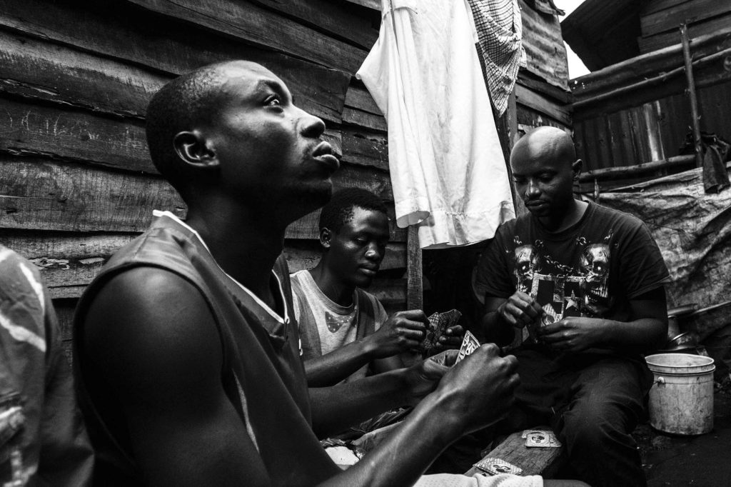 A local drug dealer plays a card game with his friends in a slum in Goma, DR Congo, 2016