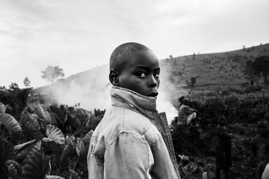 A boy stands in a field in Kitchanga, DR Congo, 2016