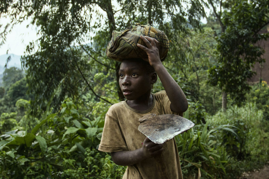 A boy returns from the field work in a rebel-held territory in the eastern DR Congo, 2016