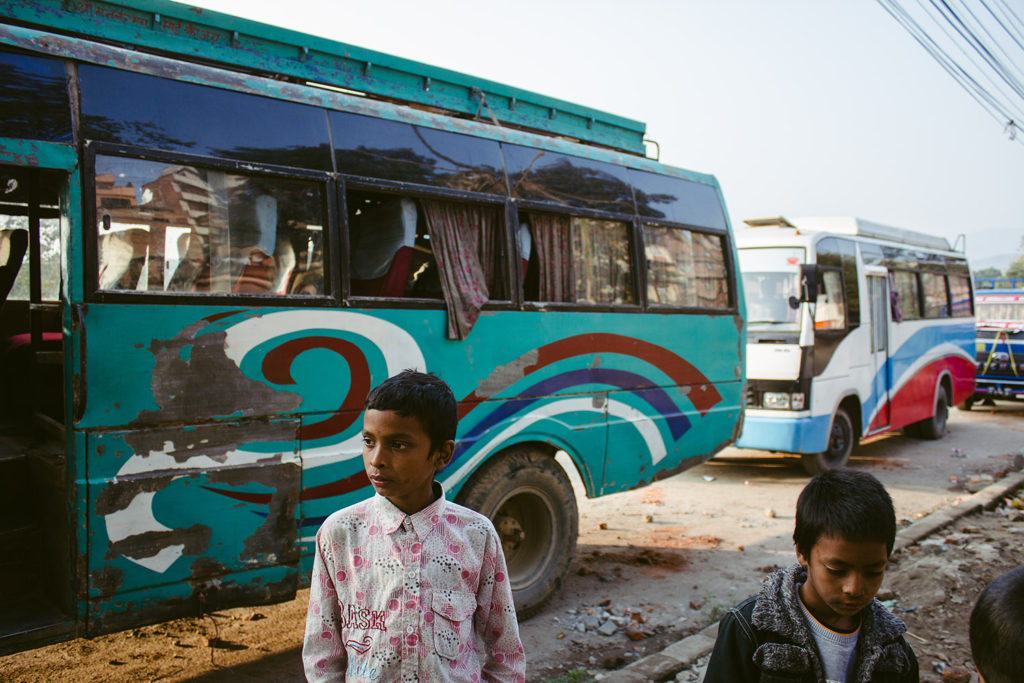 Boys stand in front of parked buses in Kathmandu, Nepal, 2015