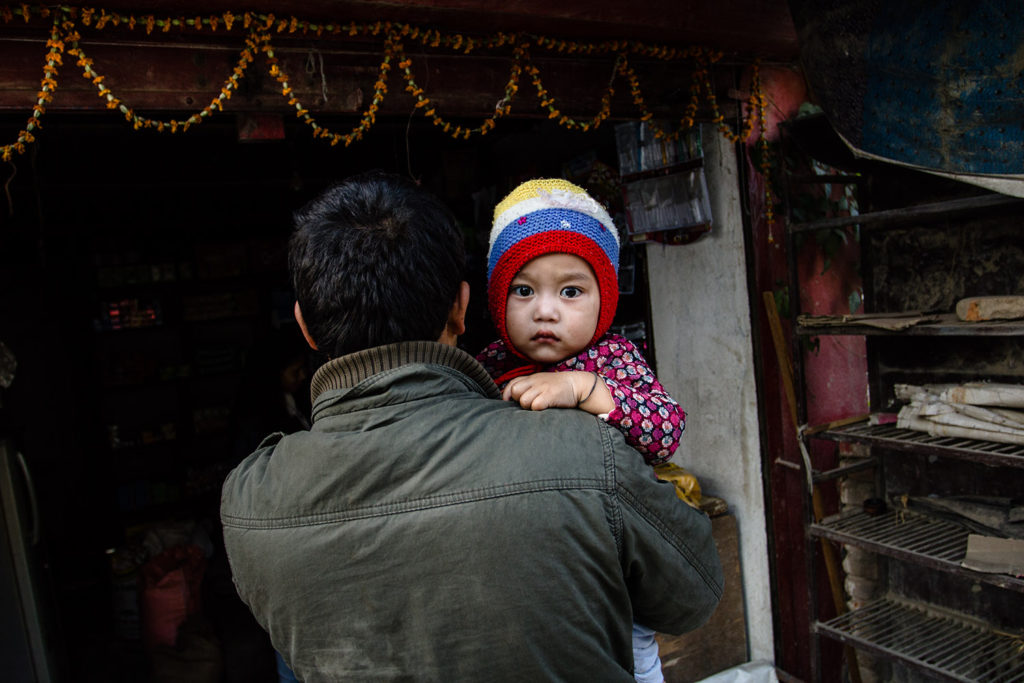 A father holds his child during Tihar festival in Kathmandu, Nepal, 2015