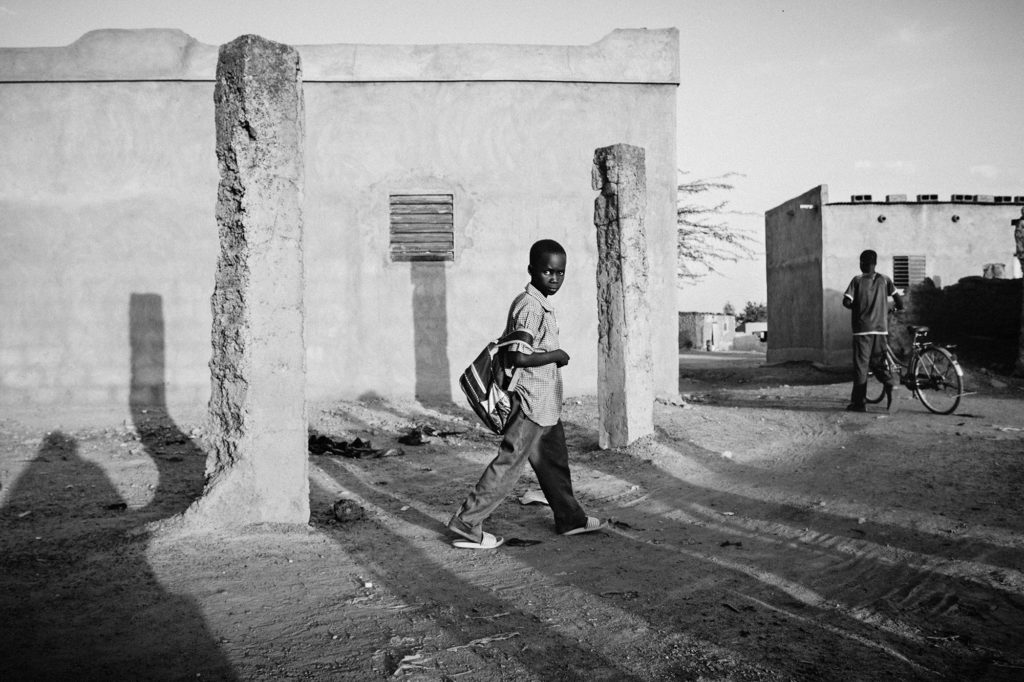 A boy on his way back from school in the outskirts of Ouagadougou, 2014